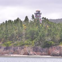 El Faro sobre la cima de un cerro de pinos