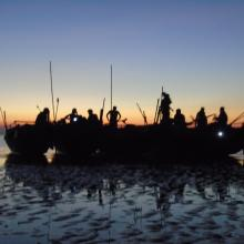 Survey team and boats at dusk