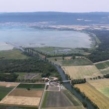La baie sur la rive orientale du lac de Neuchâtel avec le canal de la Broye, une partie du Chablais de Cudrefin (à gauche du canal) et le Fanel (à droit du canal) avec les zones humides et la lagune.