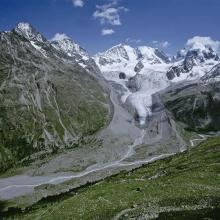 Proglacial margin of Vadret da Roseg, crossed by a brook. In the background, the Roseg glacier and the Bernina massif.