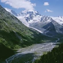 Proglacial margin crossed by a brook. In the background, the Tschierva (left) and Roseg (right) glaciers.